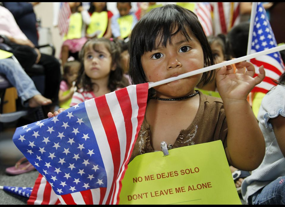 Estrella Manuel, 2, holds an American flag in her mouth during a news conference in Miami Wednesday, June 17, 2009.  Roughly