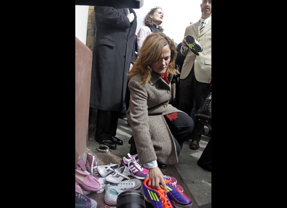 New York City Council member Melissa Mark-Viverito places a child's shoes onto a stack children's shoes, used as a symbol for