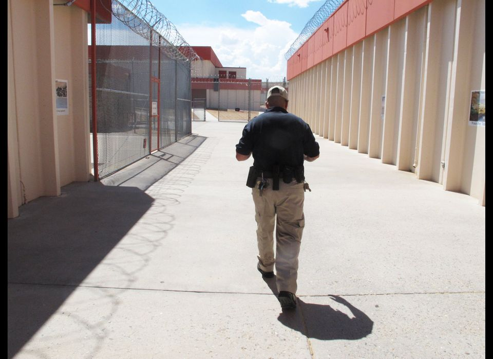 Corrections Officer Xavier Hernandez, a U.S. Army veteran who served in Iraq and Afghanistan, walks through the Central New M