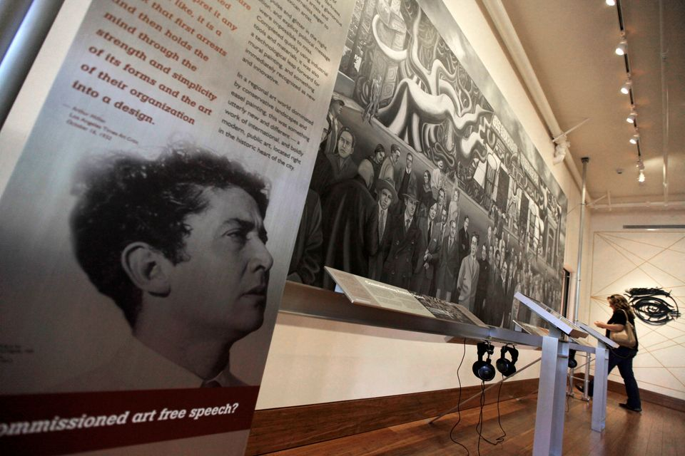 "This Oct. 4, 2012 photo shows a photo of David Alfaro Siqueiros with a black-and-white copy of his mural, ""America Tropical,"""