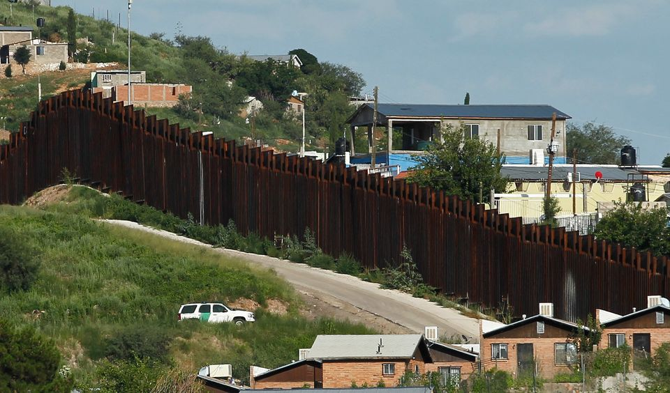 In this photo taken Thursday, Aug. 9, 2012, A U.S. Border Patrol vehicle keeps watch along the border fence in Nogales, Ariz.