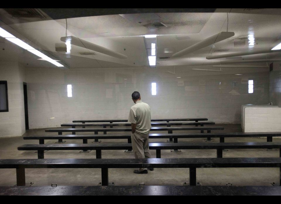 FILE - This Jan. 11, 2012 file photo shows a man waiting to be processed at a Border Patrol detention center in Imperial Beac