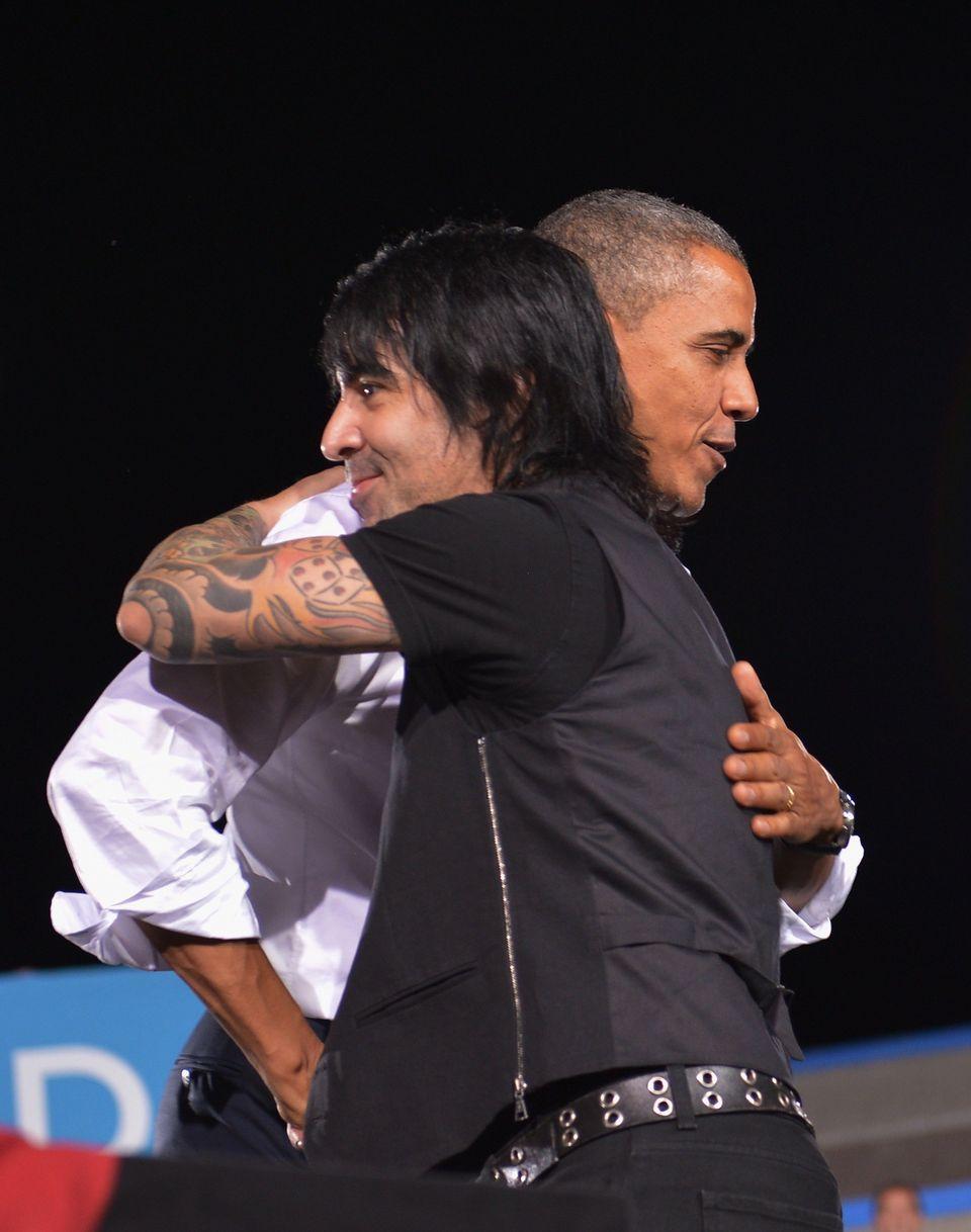 US President Barack Obama hugs Latin pop band 'Mana' member Alex Gonzalez during a campaign event September 30, 2012 at Deser