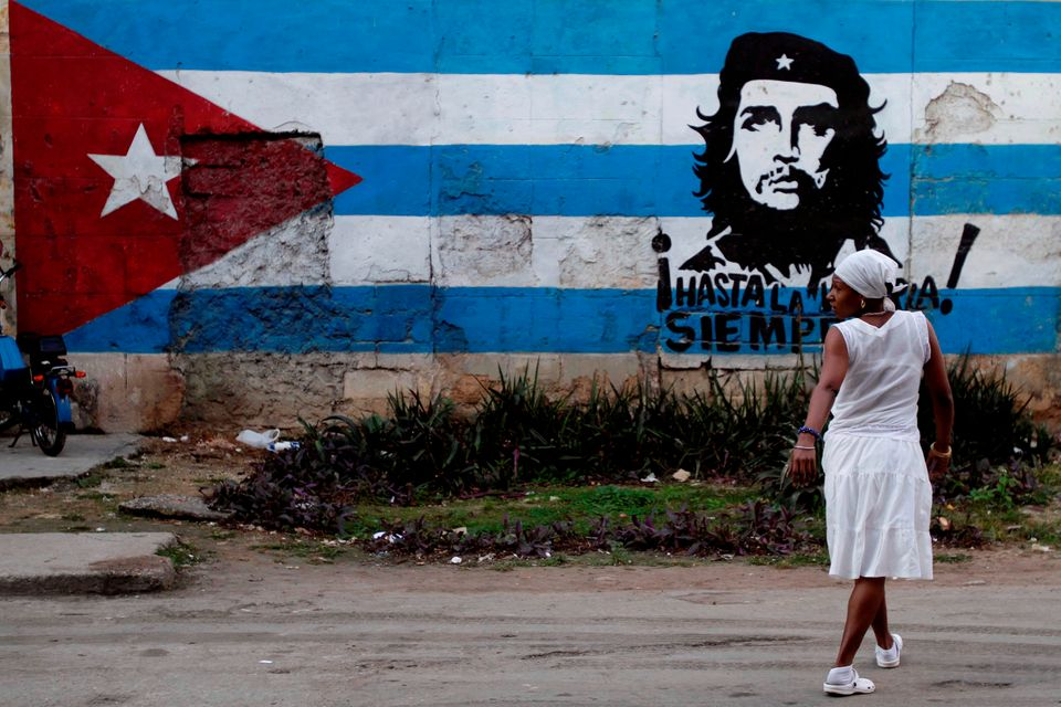 A santera looks back while crossing the street where a wall is covered with a mural of the Cuban flag and an image of Cuba's