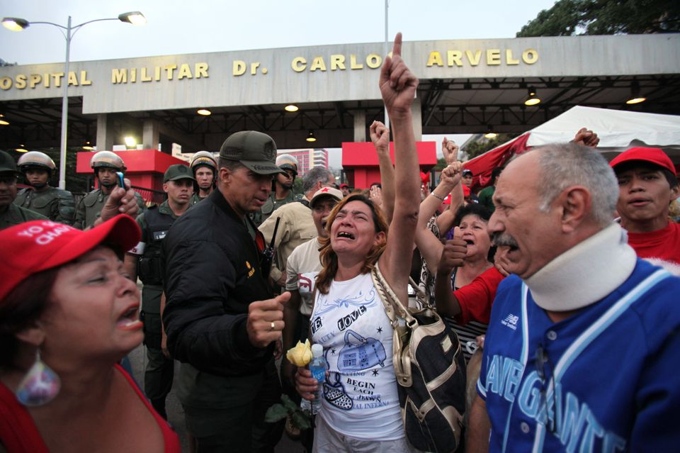Supporters of Venezuela's President Hugo Chavez react to the news that that Chavez has died, as they gather outside the milit