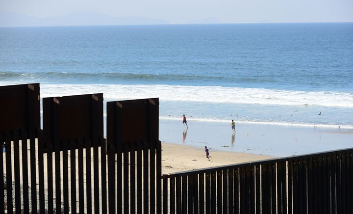 Children play on the beach at Playas de Tijuana, Mexico, across the 'border fence' which runs along the US-Mexico border some