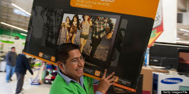 An employee carries a Polaroid Corp. 40 inch LCD television to a cash register inside Wal-Mart de Mexico SAB de CV's Bodega A