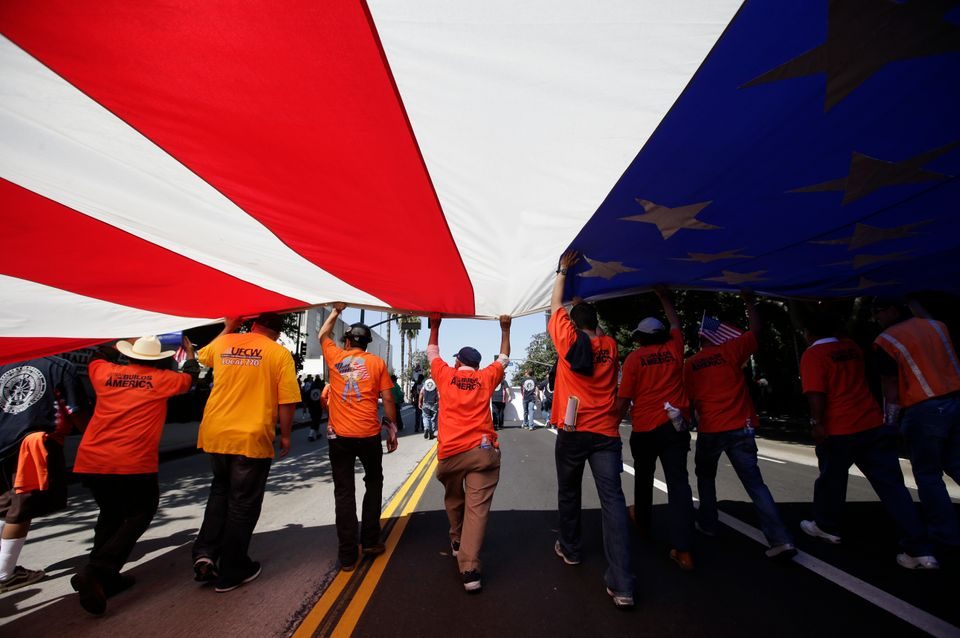 Union workers march along the street with a huge American flag during a May Day rally in Los Angeles, Wednesday, May 1, 2013.