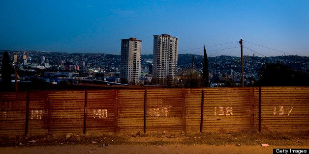 The city of Tijuana, Mexico, stands beyond the U.S.-Mexico border fence in San Diego, California, U.S. on Wednesday, March 21, 2012. Mexico's peso rose, paring its second weekly decline, amid speculation exporters are selling dollars to raise funds for tax payments before a month-end deadline. Photographer: Sam Hodgson/Bloomberg via Getty Images