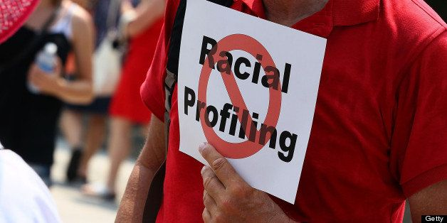 WASHINGTON - JULY 07: A man holds a sign against racial profiling during a protest with Community and faith leaders from Ariz
