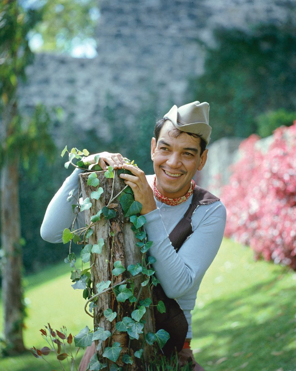 Mexican actor and comedian Cantinflas (1911 - 1993), born Mario Moreno Reyes, looking Puckish behind an ivy-covered stump, ci
