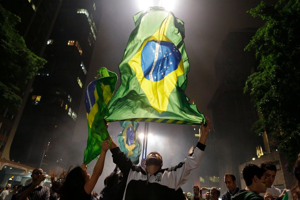 Demonstrators wave their country's national flag on Paulista Avenue where crowds gathered to celebrate the reversal of a fare