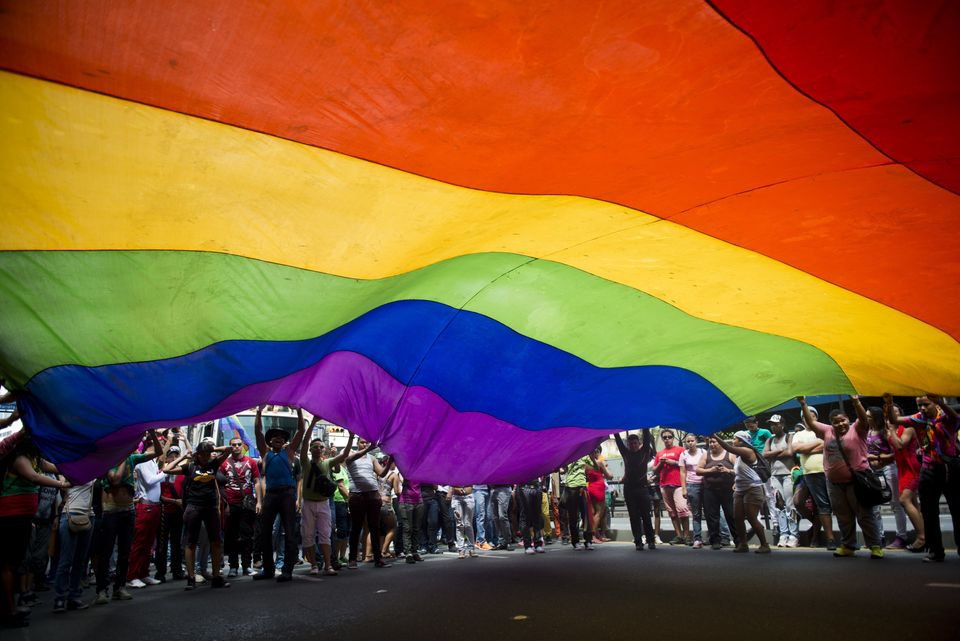 People lift a giant rainbow flag during the 35th Annual Gay Pride March in Caracas, June 30, 2013