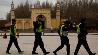 A police patrol walk in front of the Id Kah Mosque in the old city of Kashgar, Xinjiang Uighur Autonomous Region, China, March 22, 2017.  REUTERS/Thomas Peter
