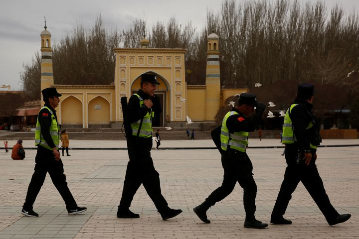 A police patrol walk in front of the Id Kah Mosque in the old city of Kashgar, Xinjiang Uighur Autonomous Region, China.