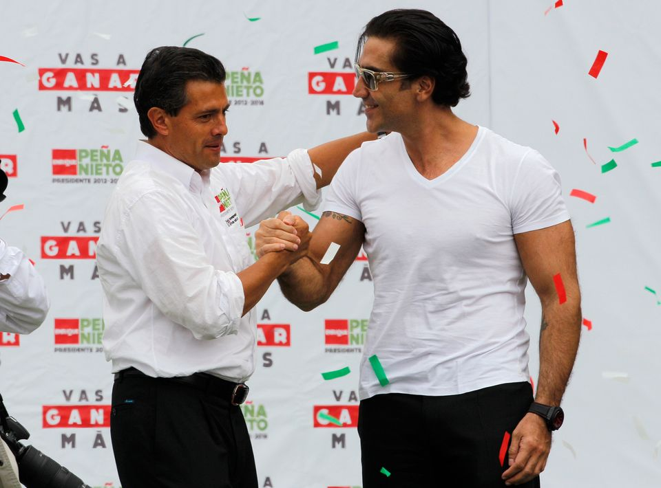 Presidential candidate Enrique Pena Nieto, left, of the Institutional Revolutionary Party (PRI), shakes hands with folk music