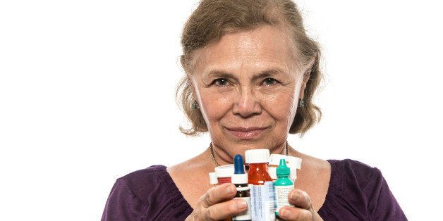 serious senior hispanic woman posing holding her prescription medicines in her hands on white background