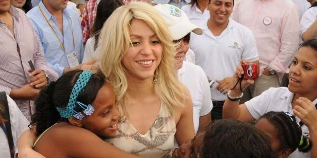 Colombian singer Shakira (C) greets children upon arrival for the launching of the 'Primero es lo primero' programme, in Cart
