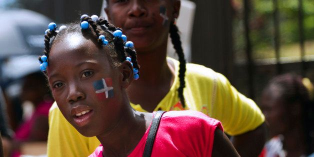 Haitians with the Dominican flag painted on their cheeks demonstrate in front of the Central Electoral Board to demand their
