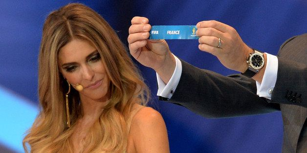 FIFA Secretary General Jerome Valcke shows the name of Belgium next to presenter Fernanda Lima during the final draw of the g