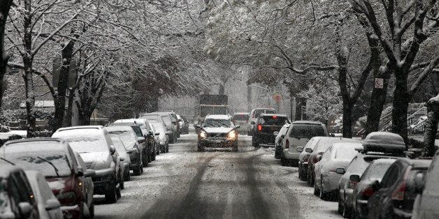 NEW YORK, NY - DECEMBER 10:  A car drives up a snow covered street on December 10, 2013 in the Brooklyn borough of New York C