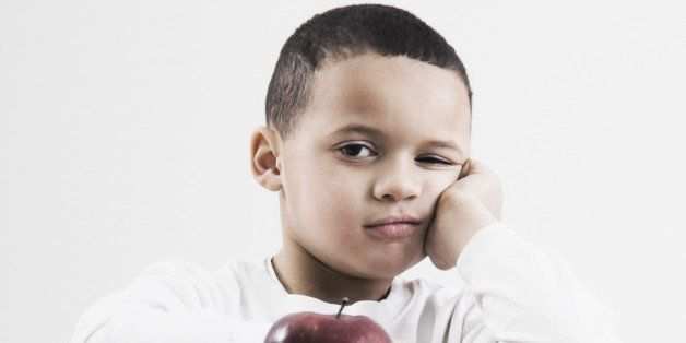 african boy at desk with apple