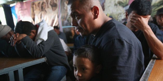 NOGALES, MEXICO - MARCH 10:  Javier Guerrero from Mexico attends a Catholic Mass with his visiting son, Javier Jr. (3), a U.S