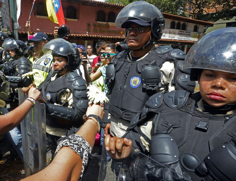 Students give flowers to National Police members during an anti-government protest in Caracas on February 17, 2014. Venezuela