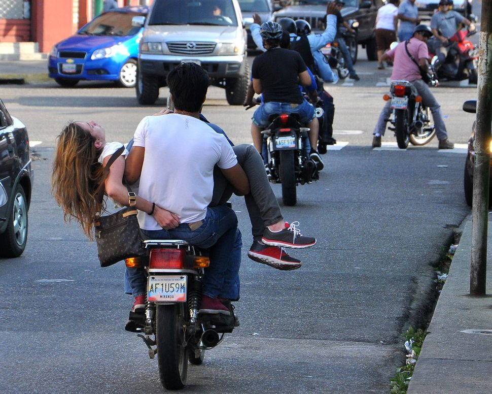 A motorcyclist carries Venezuelan model Genesis Carmona, injured during an anti-government protest in Valencia on February 18