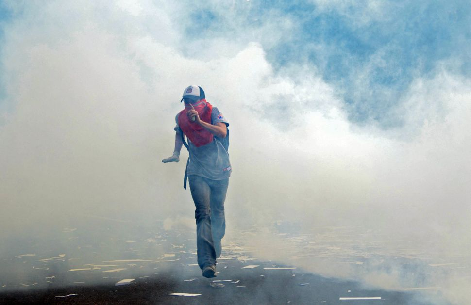 A protestor throws stones during an anti-government demo, in Caracas on February 19, 2014. Venezuelan President Nicolas Madur