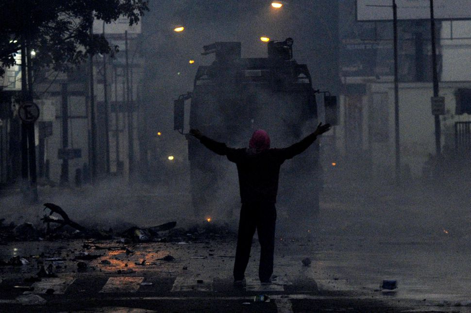 A protestor confronts riot policemen during an anti-government demo, in Caracas on February 19, 2014. Venezuelan President Ni