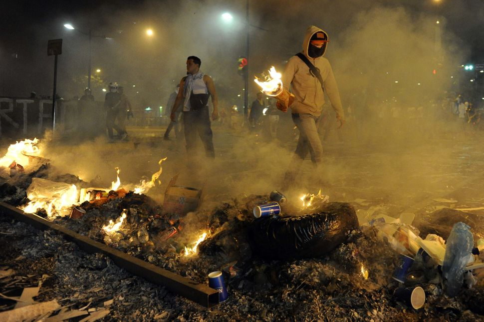 Protestors light fires during an anti-government demo, in Caracas on February 19, 2014. Venezuelan President Nicolas Maduro,
