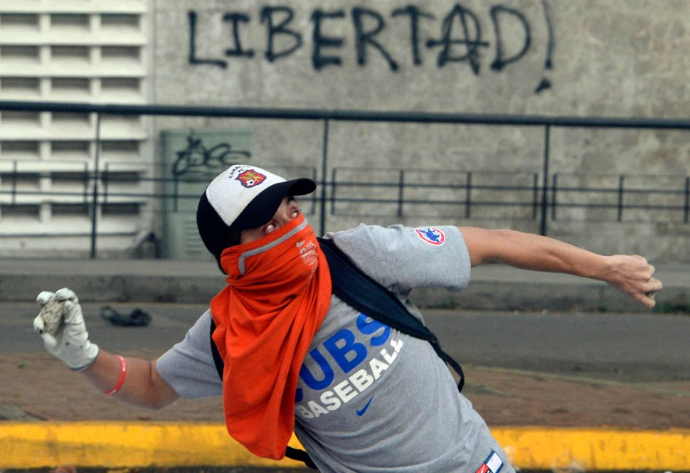 A Venezuelan anti-government student throws stones to riot police during a protest, in Caracas on February 19, 2014. Four peo