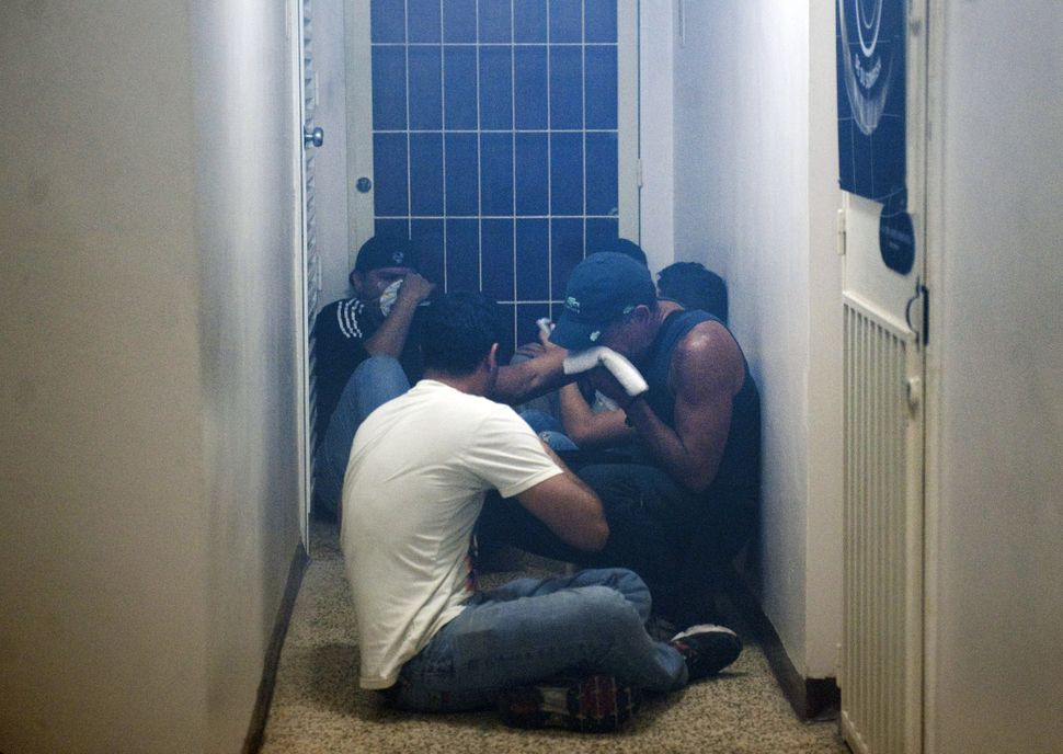 Students hide in a building during an anti-government demo, in Caracas on February 19, 2014. Venezuelan President Nicolas Mad