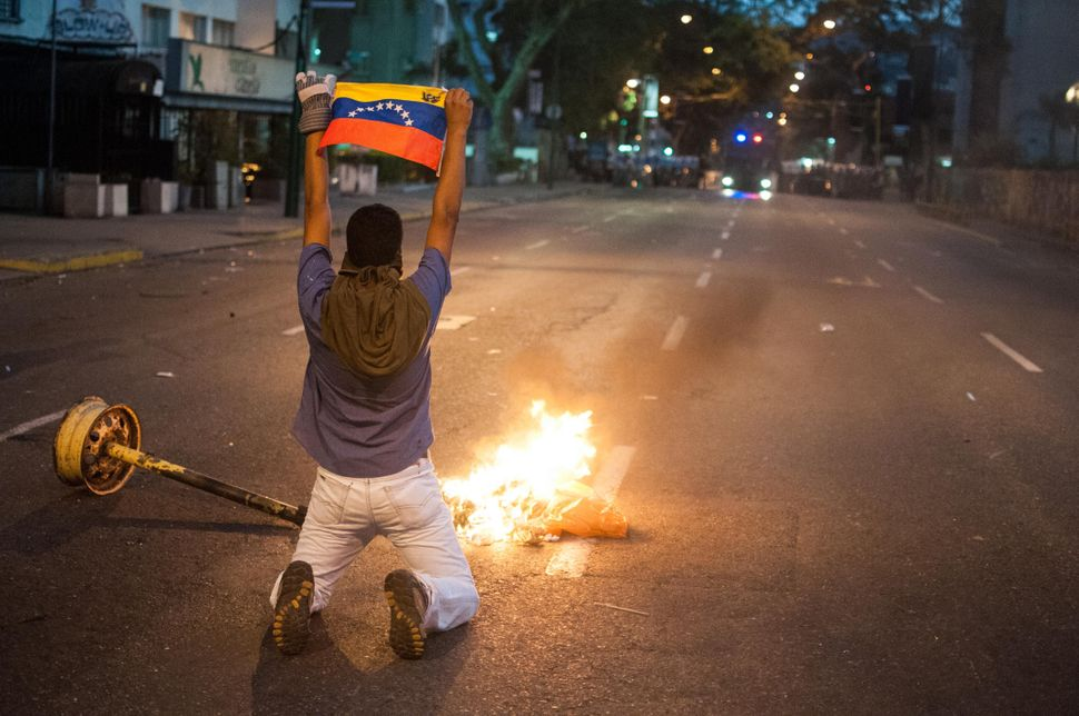 An anti-government protester holds up a national flag during a demonstration in the Altamira neighborhood of Caracas, Venezue