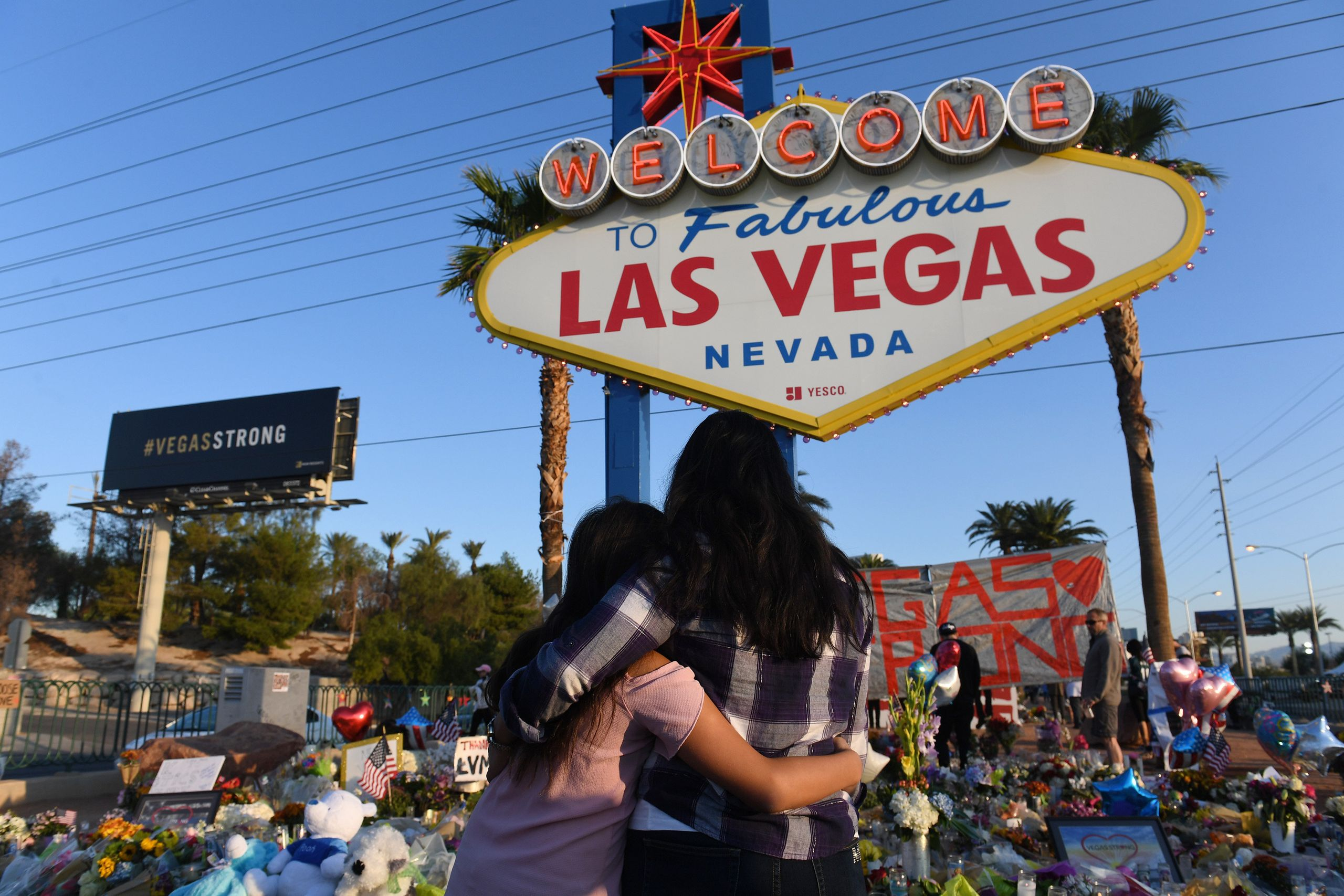 People visit a makeshift memorial to the victims of the Oct. 1, 2017, massacre at an outdoor concert in Las Vegas. The g