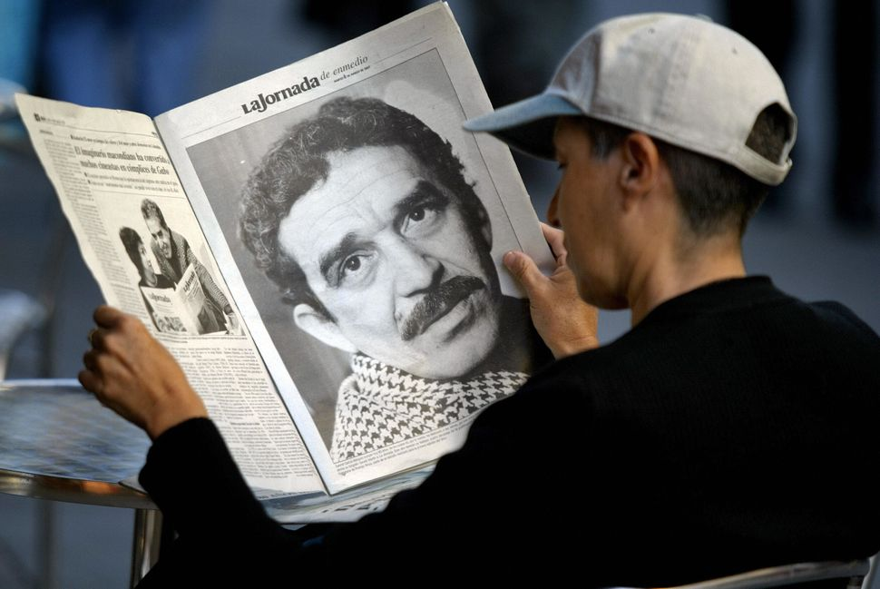 A young Mexican sitting in a cafe reads a newspaper which offers a special supplement dedicated to Colombian writer and Nobel