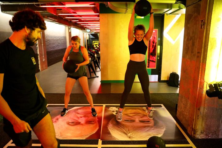 A gym member drop balls on images of Britain's Prime Minister Theresa May and Labour leader Jeremy Corbyn during a Brexfit gy