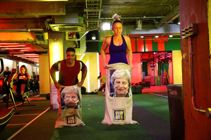 Gym members jump in sacks containing an image of Britain's Prime Minister Theresa May during a Brexfit gym class.