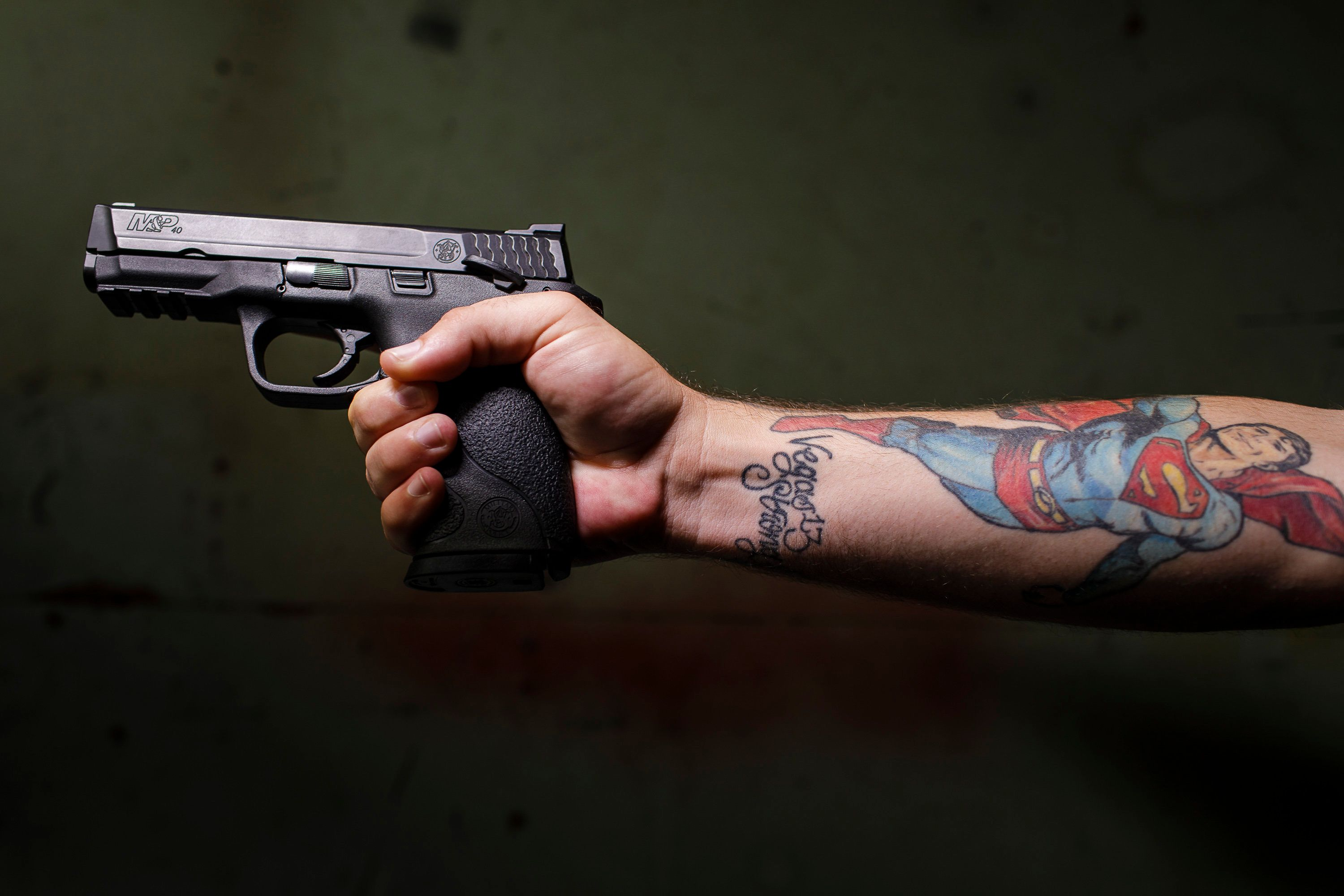 "EUGENE, OR – SEPTEMBER 5th, 2018: Veteran and longtime gun owner Shane Hooper poses for portraits with his Smith & Wesson M&P 40 at his home in Eugene, OR.  Hooper has been trying (unsuccessfully) to get rid of the two guns he currently owns after surviving the 2017 Las Vegas shooting at the Route 91 Harvest music festival on the Las Vegas Strip in Nevada, that left 58 people dead and 851 injured. Hooper got a ""Vegas Strong"" tattoo two weeks after the shooting. CREDIT: Leah Nash for The Huffington Post"