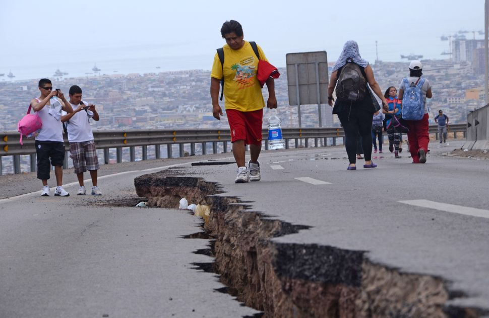 People walk along a cracked road in Iquique, northern Chile, on April 2, 2014 a day after a powerful 8.2-magnitude earthquake