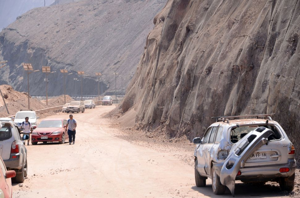 Damaged cars on a road near Iquique, northern Chile, on April 2, 2014 a day after a powerful 8.2-magnitude earthquake hit off