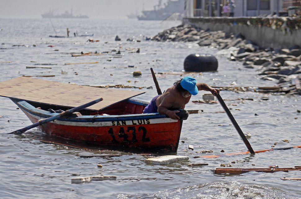 A fisherman looks to salvage any remains destroyed overnight in the port of Iquique, in northern Chile, on April 2, 2014 afte