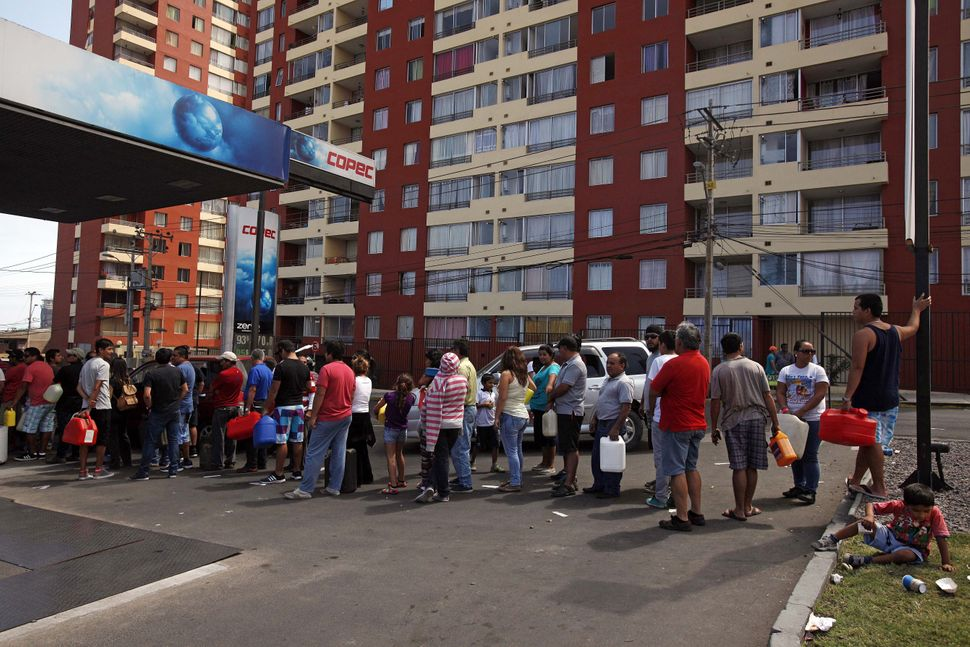 People stand in line to buy fuel in Iquique, in northern Chile, on April 2, 2014 a day after a powerful 8.2-magnitude earthqu
