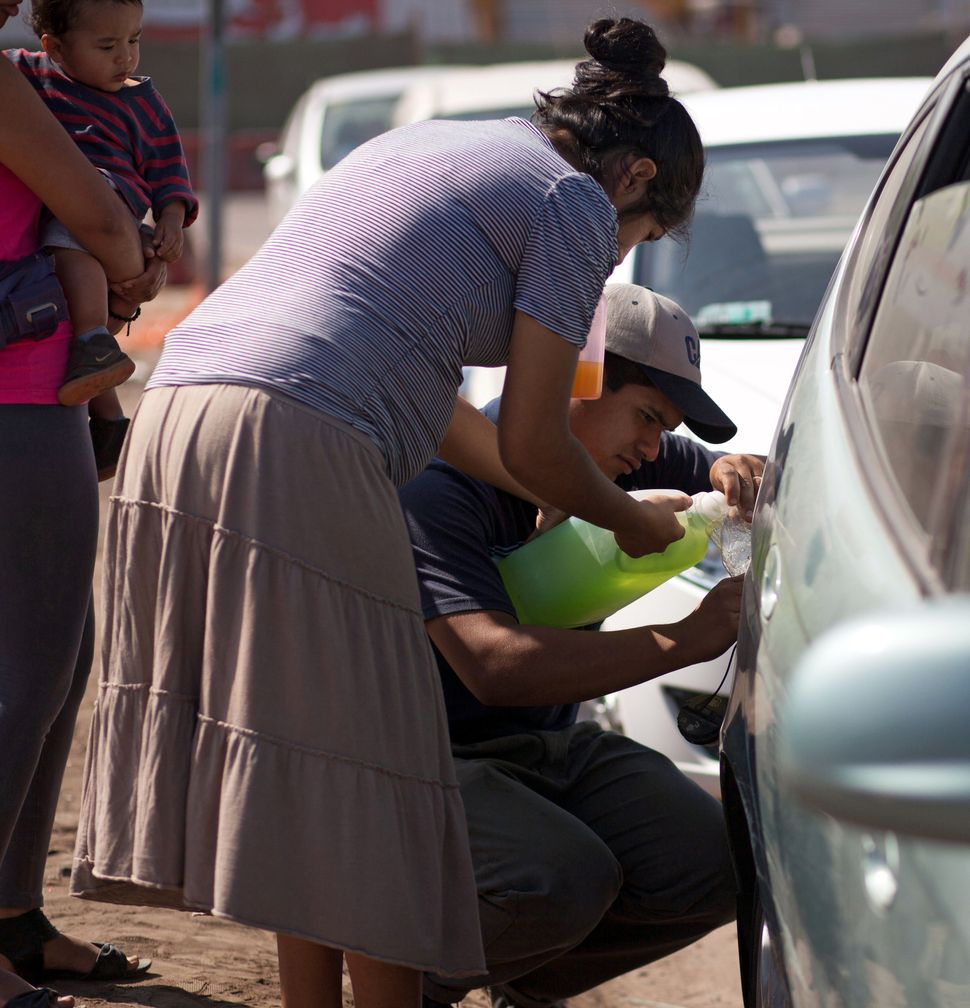 A family put fuel in a vehicle in Iquique, northern Chile, on April 2, 2014, a day after a powerful 8.2-magnitude earthquake