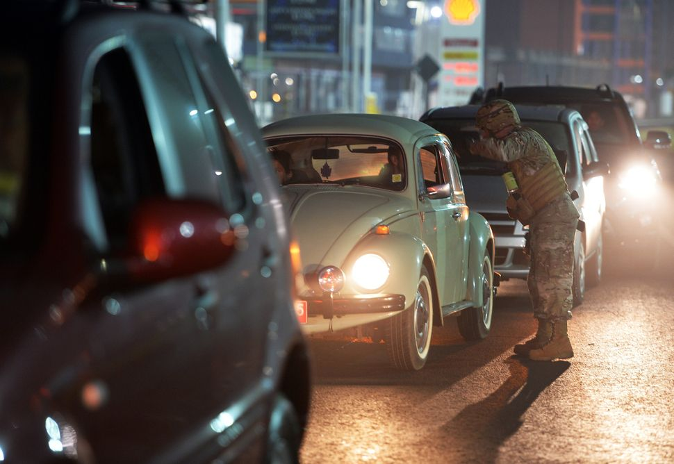 A Chilean Army soldier speaks with a car driver as he guards a gas station in Iquique, 1,950 kilometres north of Santiago, wh