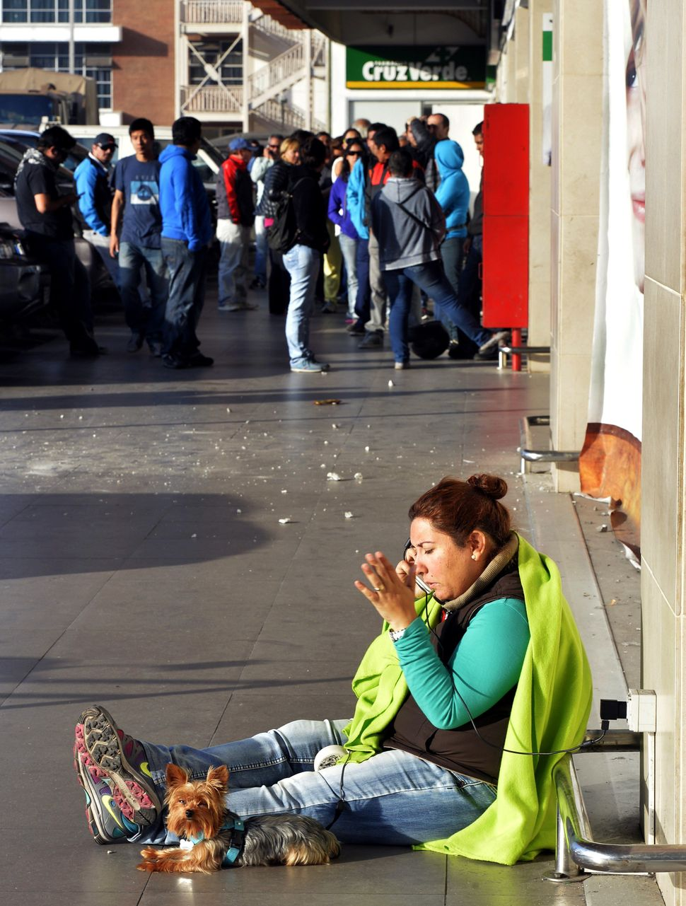A woman uses an electric outlet to use her mobile phone as people queue in front of a major grocery store in Iquique, 1,950 k