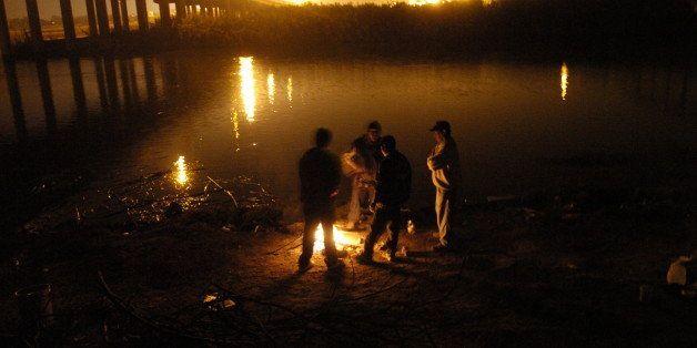 PIEDRAS NEGRAS DEC. 11, 2006 -- Migrants wait along the shore of the Rio Grande River in Piedras Negras, Mexico, Monday, Dec.