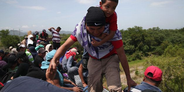 IXTEPEC, MEXICO - AUGUST 06:  Central American immigrants arrive on top of a freight train for a stop on August 6, 2013 in Ix