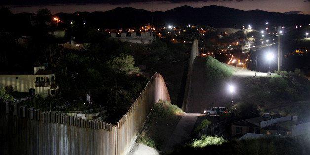 NOGALES, AZ - JULY 6: The border wall is illuminated at night July 6, 2012 in Nogales, Arizona. The president-elect...